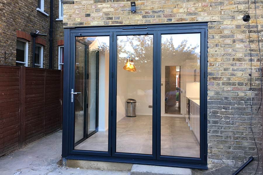 dark grey Visofold 1000 corner bi fold doors with fixed screen for kitchen extension in London